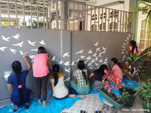 Colleagues and beneficiaries of Eden Ministry pain the wall of the centre together